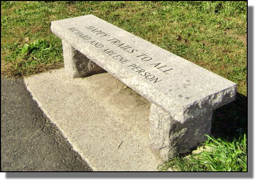 A photo of a granite bench along the Milford Upper Charles trail.  The engraving on the bench reads 'Happy Trails to all  Richard and Arlene Person'